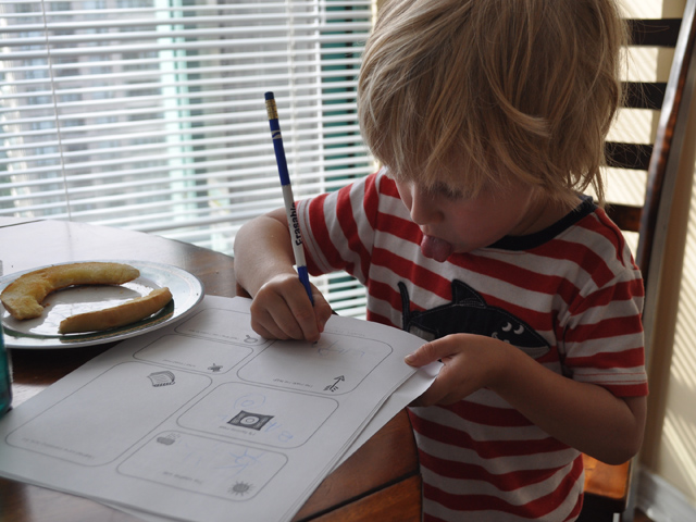 Here's F working on the travel journal while eating breakfast. I love that he's sticking out his tongue! I also love that my son has those PJs.